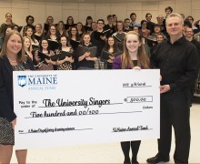 The University Singers accept a $500 check from Christina Caron of the UMaine Annual Fund